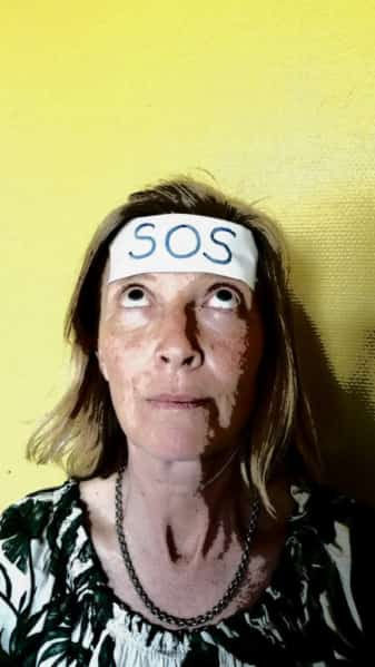 woman with 'SOS' on sticker on foorhead