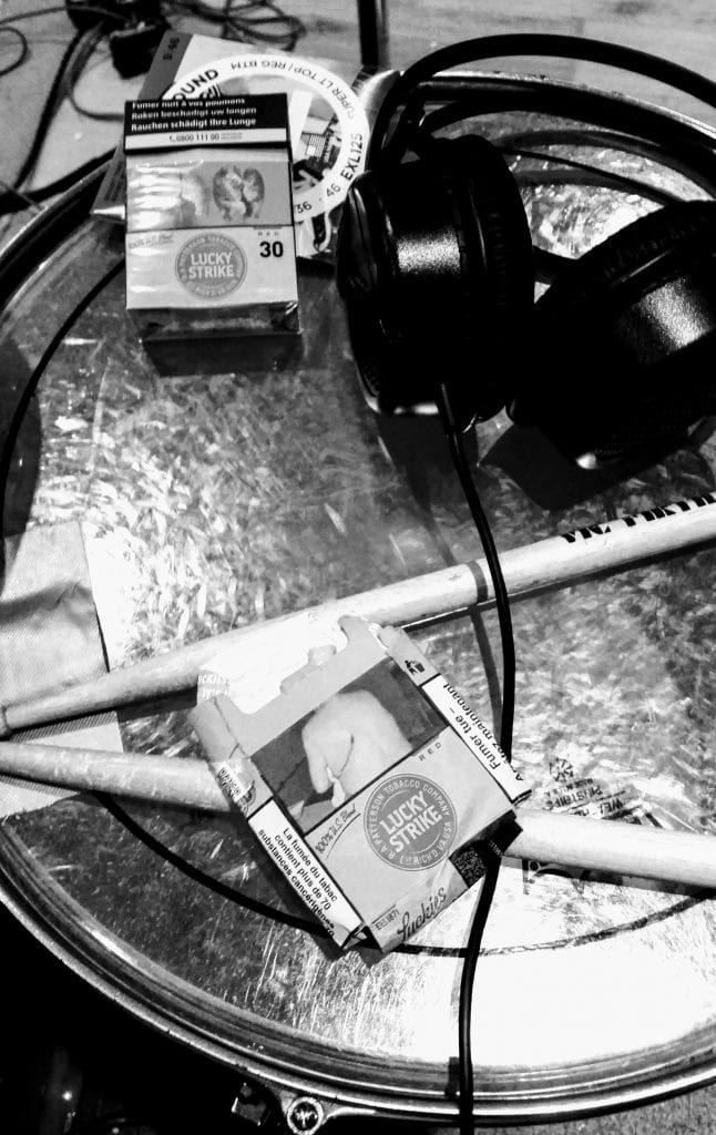 Cigarttes and drum sticks on a drum
