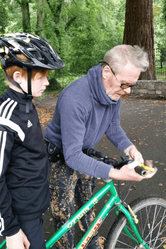 Boy on bike with father figure adjusting his brakes outdoors