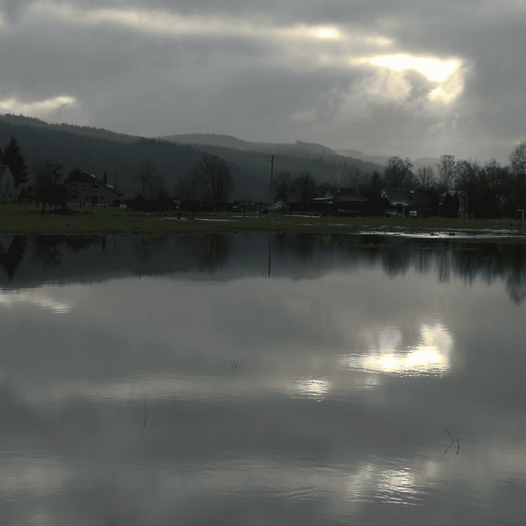 Reflections in a flooded field - a cloudy sky with sunshine and trees
