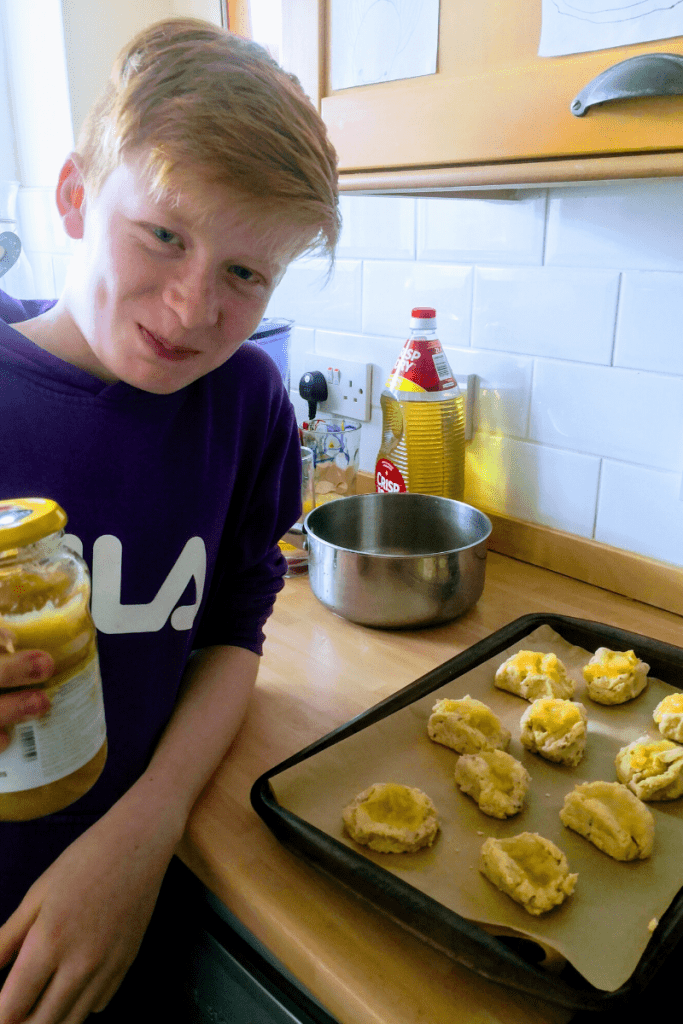 A boy in the kitchen with his proud baking creations