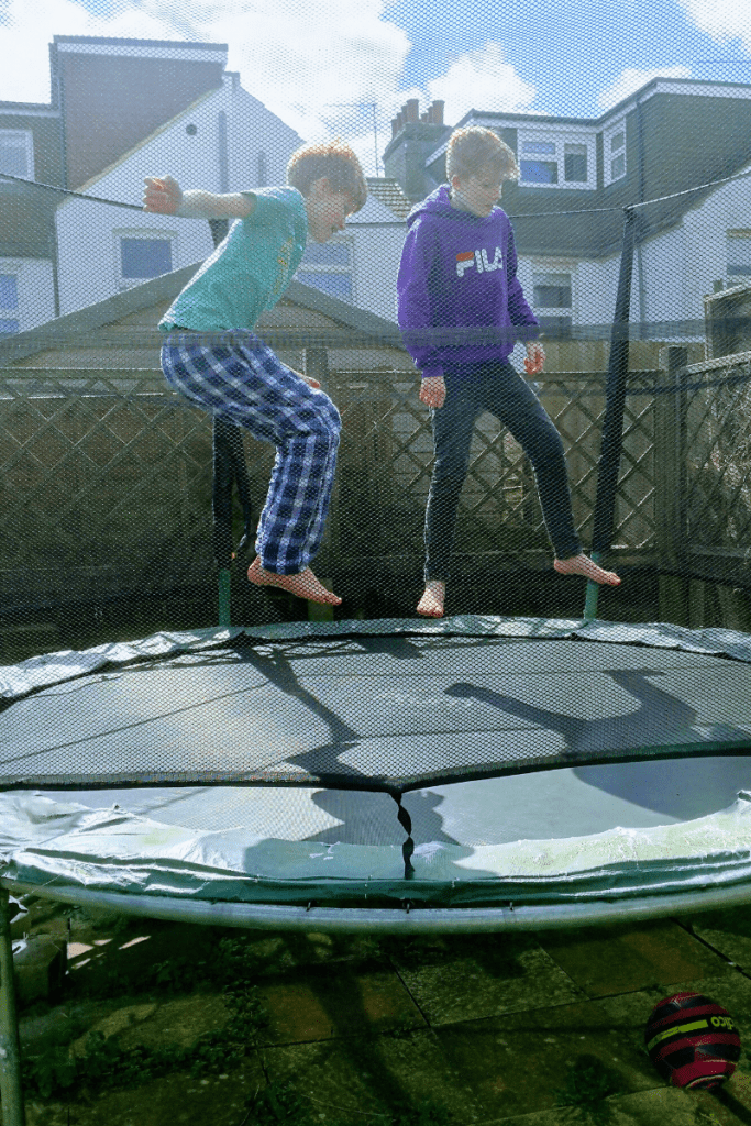 Two happy children bouncing on trampoline