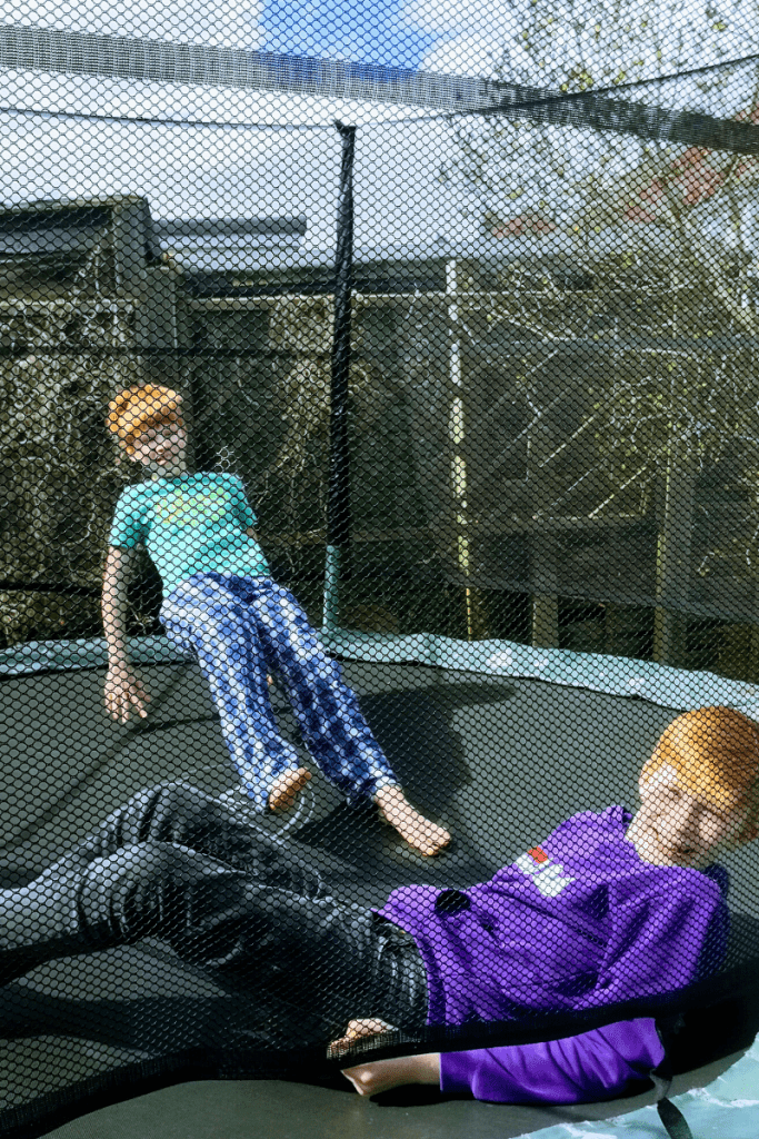 Two children happily bouncing on trampoline