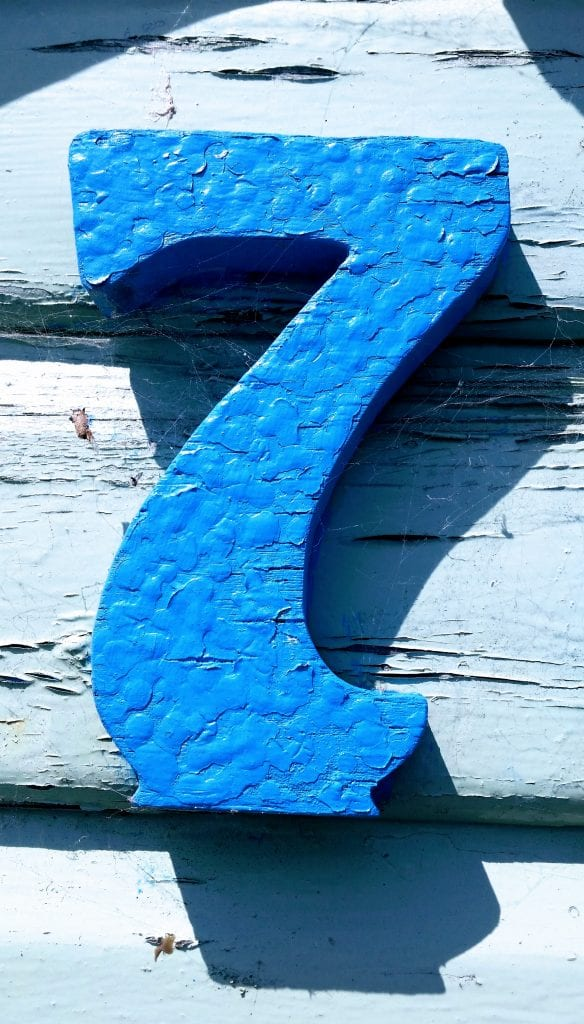 A blue figure 7 on a wooden background