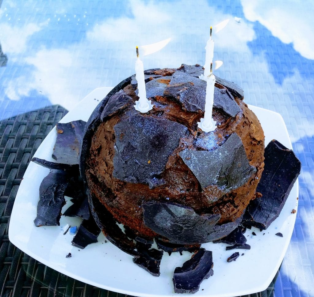 asteroid cake with broken chocolate shell and three candles